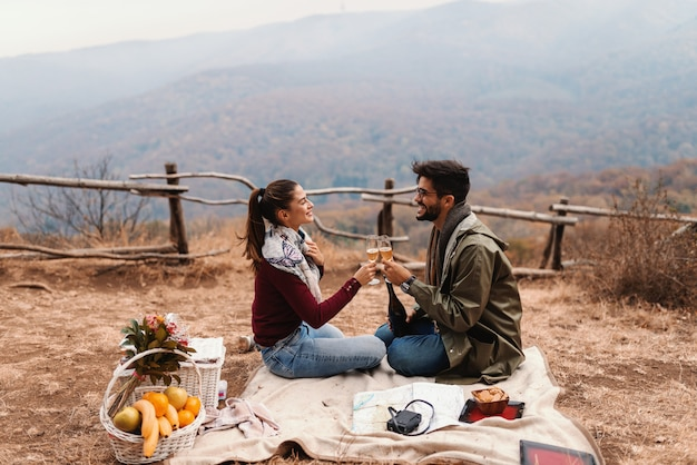 Casal comemorando aniversário no piquenique. casal sentado no cobertor e torcendo com vinho. tempo de outono.