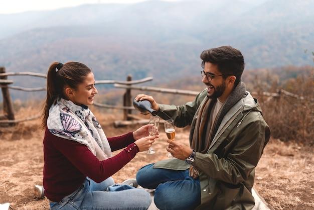 Casal comemorando aniversário no piquenique. homem derramando champanhe em copos. tempo de outono.