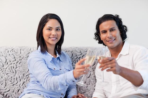 Casal comemorando com vinho espumante no sofá