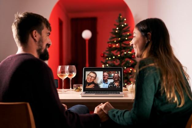 Casal comemorando o natal em quarentena devido ao dia 19, fazendo uma videochamada para os pais e sogros. novo normal em tempos de coronavírus.