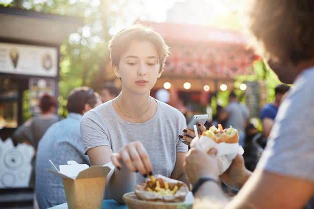 Casal comendo batatas fritas e hambúrguer em um dia ensolarado de verão no parque em um faire se divertindo.
