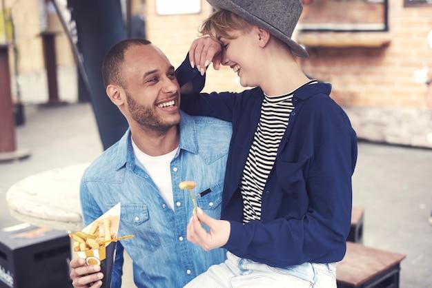 Casal comendo batatas fritas saborosas ao ar livre