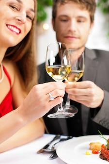 Casal comendo e bebendo em muito bom restaurante