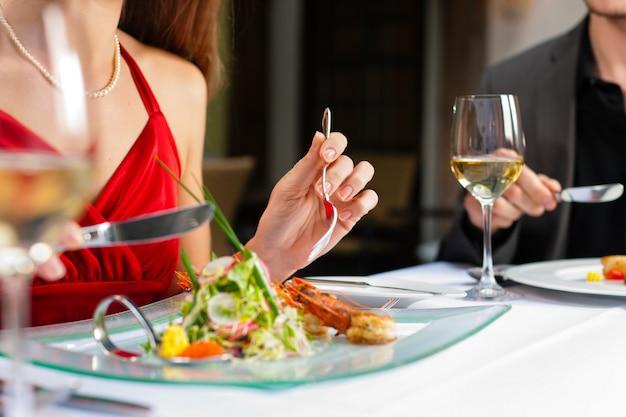 Casal comendo e bebendo em um restaurante muito bom
