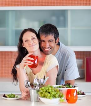 Casal comendo e bebendo na cozinha