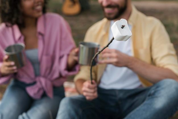 Casal comendo marshmallow enquanto acampa