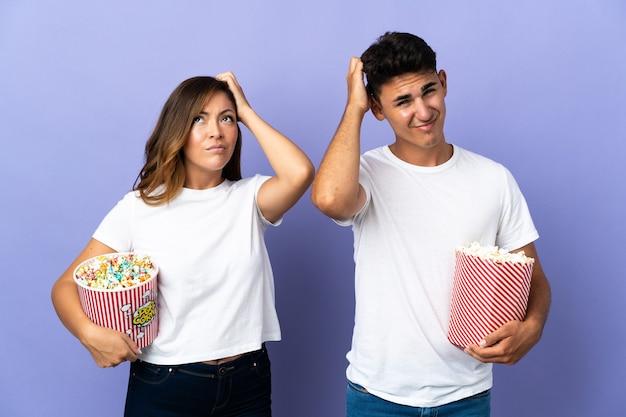 Casal comendo pipoca enquanto assiste a um filme em roxo tendo dúvidas enquanto coça a cabeça