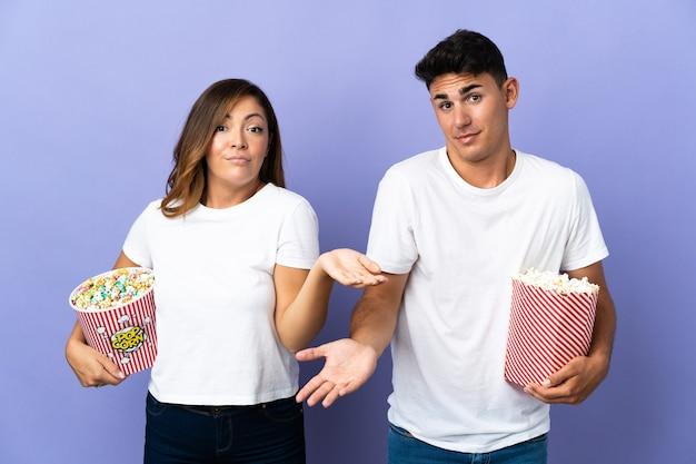 Casal comendo pipoca enquanto assiste a um filme em roxo tendo dúvidas enquanto levanta as mãos e os ombros