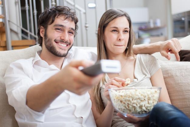 Casal comendo pipoca enquanto assiste a um filme