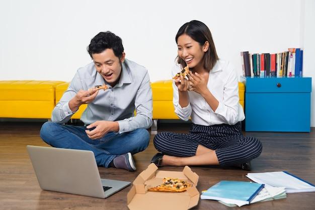 Casal comendo pizza asiática feliz olhando para laptop