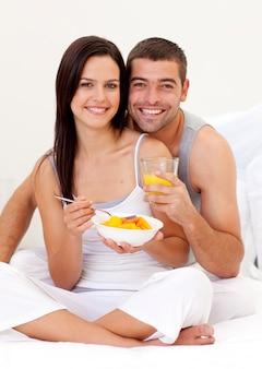 Casal comendo suco de fruta e laranja na cama
