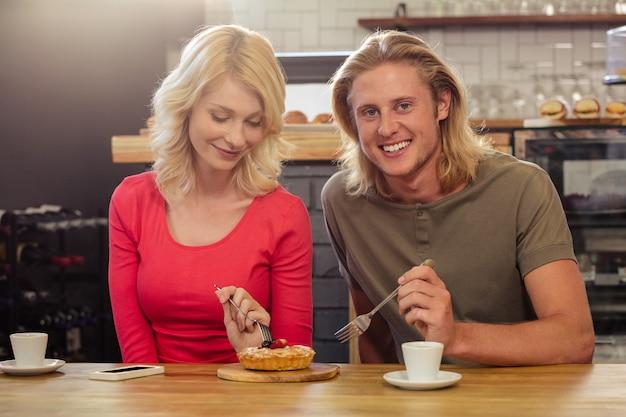 Casal comendo um bolo juntos