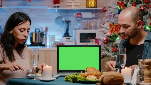 Casal comendo uma refeição festiva vendo uma tela verde horizontal