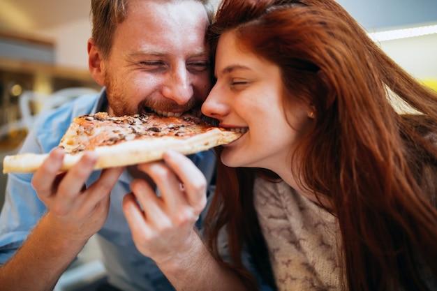 Casal compartilhando pizza e comendo juntos alegremente