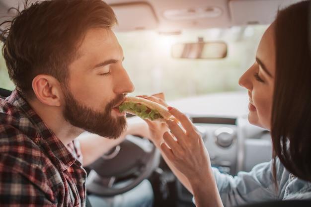 Casal compartilhando refeição uns com os outros no carro