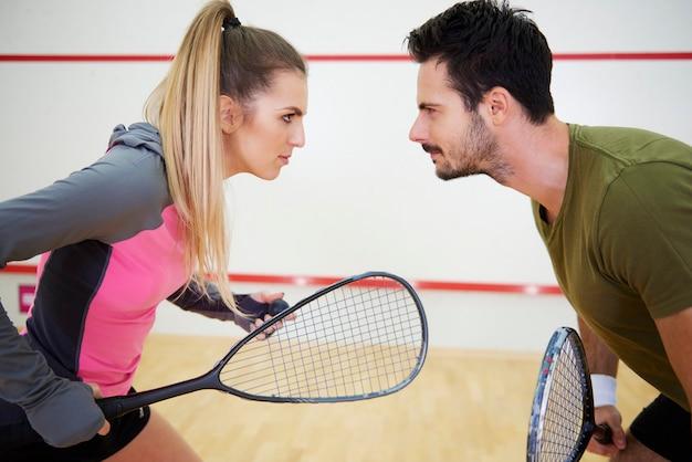 Casal competitivo jogando squash