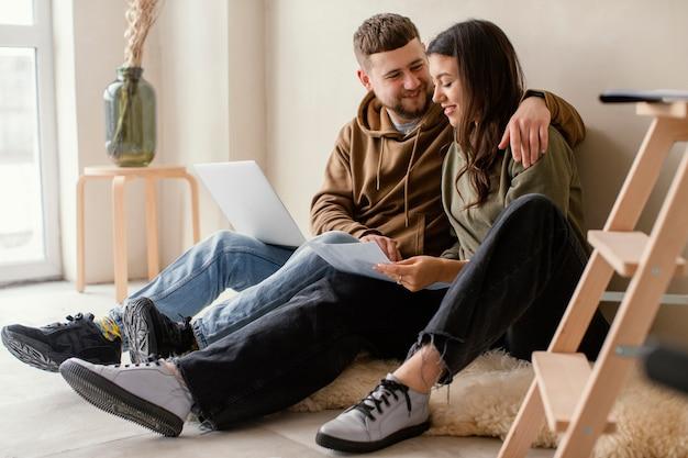 Casal completo com laptop dentro de casa