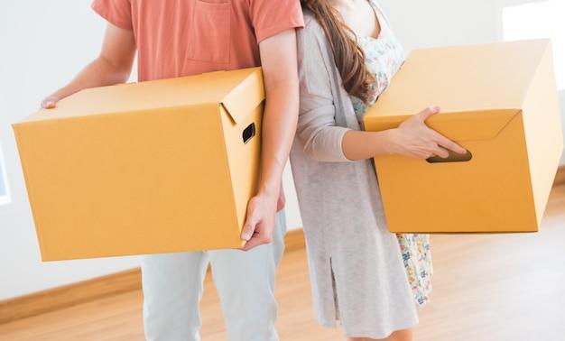 Casal compra uma nova casa. movendo a caixa para dentro de casa.