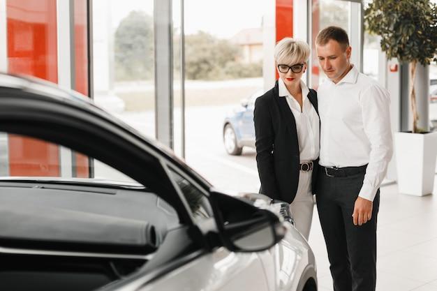 Casal comprando o carro. par em um salão de beleza do carro.