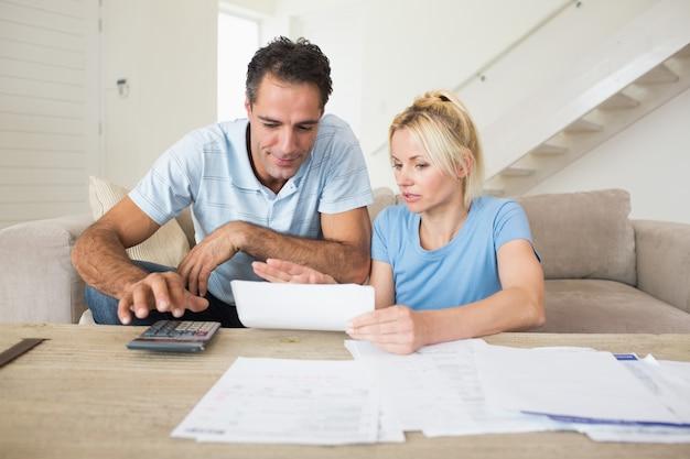 Casal concentrado com contas e calculadora na sala de estar