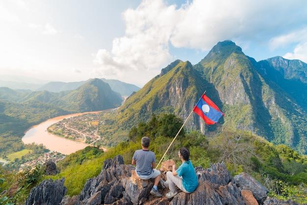 Casal conquistando o topo da montanha na vista panorâmica de nong khiaw sobre o vale do rio nam ou laos bandeira nacional paisagem de montanha