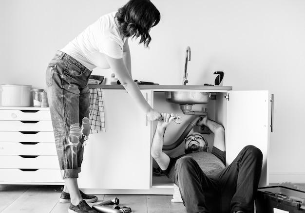 Casal consertando pia de cozinha