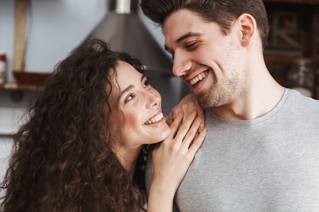 Casal contente, homem e mulher, sorrindo e se abraçando na cozinha moderna de casa