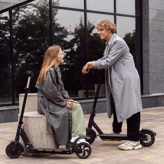 Casal conversando ao ar livre com patinetes elétricas