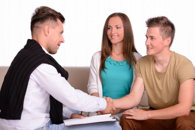 Casal conversando com o psicólogo de família no quarto.