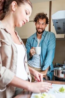 Casal conversando enquanto esposa prepara o jantar
