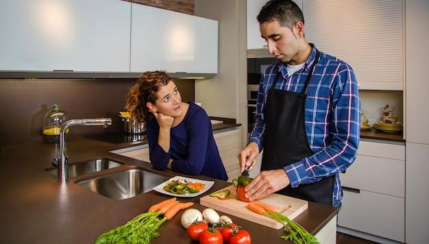 Casal conversando na cozinha enquanto o marido corta verduras para preparar comida