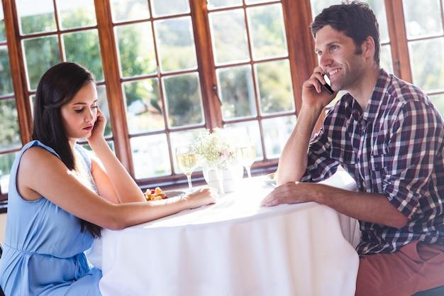 Casal conversando no celular em restaurante