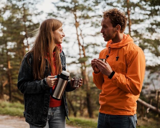 Casal conversando sobre uma bebida quente durante uma viagem