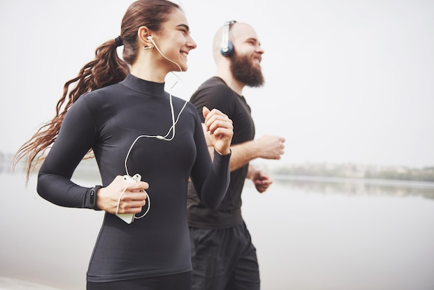Casal correndo e correndo ao ar livre no parque perto da água. jovem barbudo homem e mulher exercitando juntos de manhã