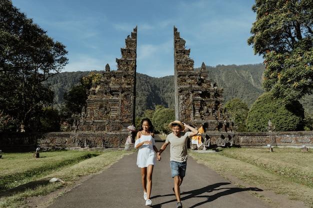Casal correndo juntos através do portão tradicional de bali