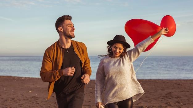 Casal correndo na beira-mar com balões de coração vermelho