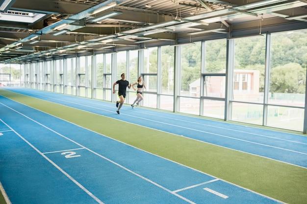 Casal correndo na pista coberta no ginásio
