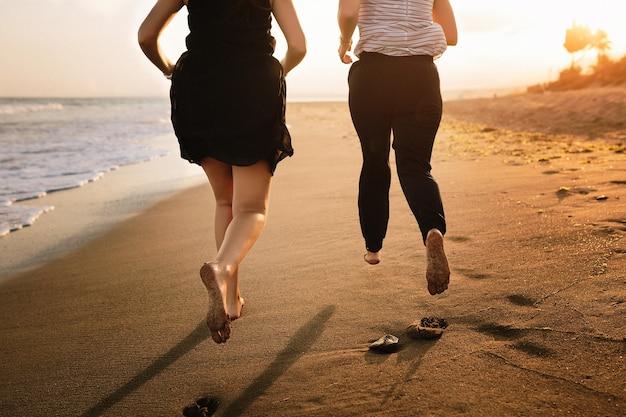 Casal correndo na praia ao pôr do sol