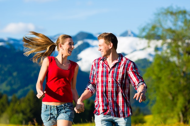 Casal correndo no prado com montanha