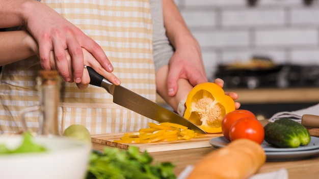 Casal cortando pimenta na cozinha juntos