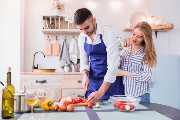 Casal cortando pimenta para salada na placa de madeira