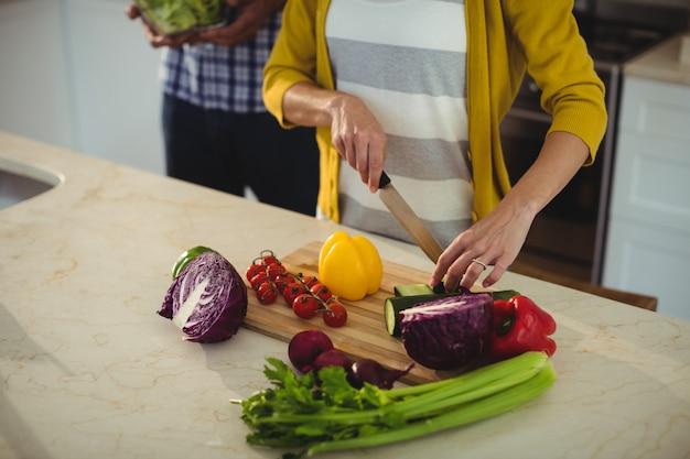 Casal cortar legumes na cozinha em casa