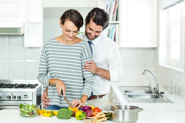 Casal cortar legumes na mesa na cozinha