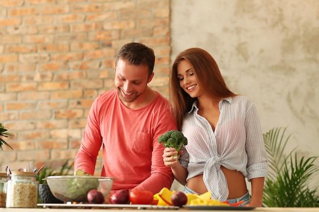 Casal cozinhando legumes na cozinha