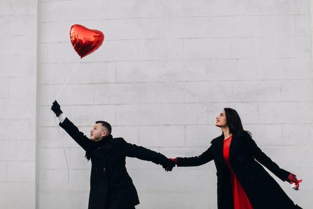 Casal criativo com balão vermelho