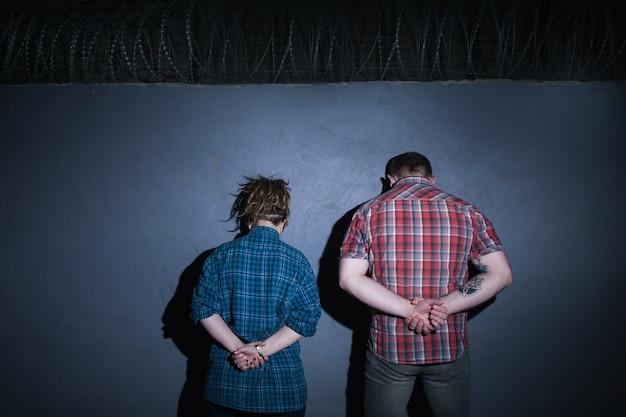 Casal criminoso. parceiros no crime. detido pessoas irreconhecíveis em fundo azul, jovens presos à noite, mãos atrás das costas, conceito culpado