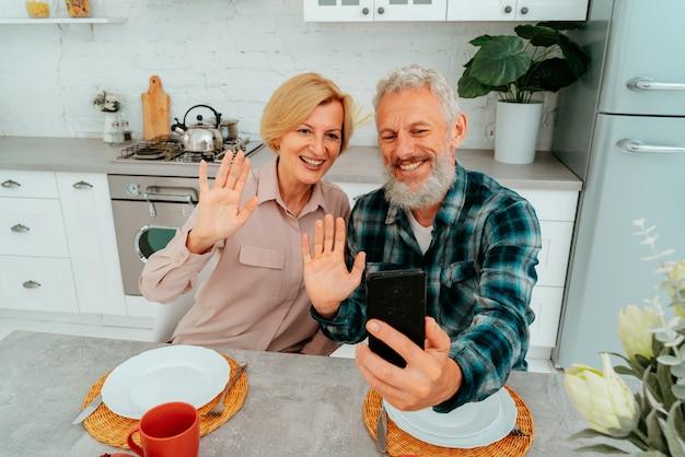 Casal cumprimenta amigos com uma videochamada durante o café da manhã