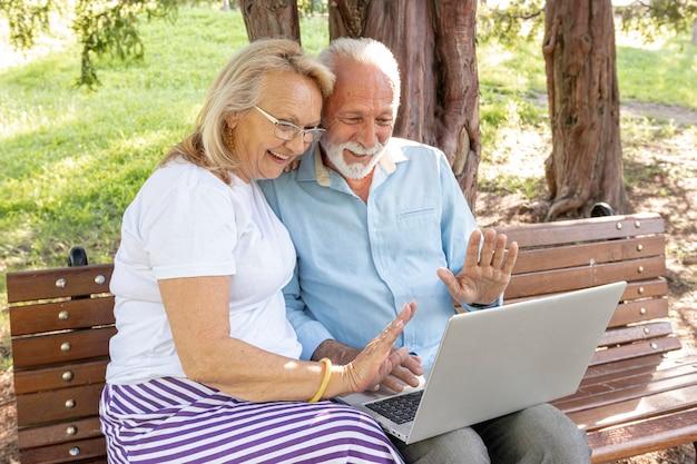 Casal cumprimentando alguém no laptop