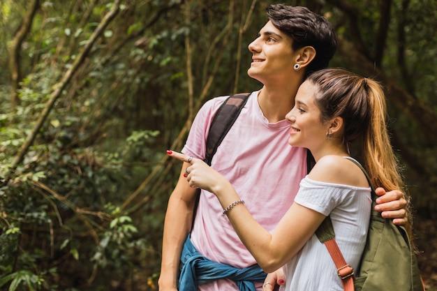 Casal curtindo a vista olhando a paisagem da floresta