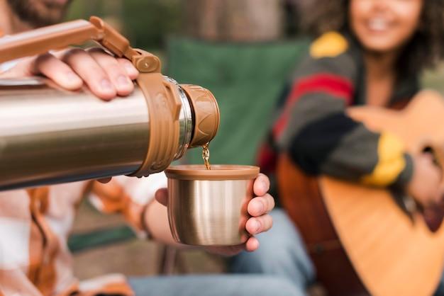 Casal curtindo acampar ao ar livre com violão e bebida quente